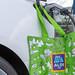 Grüne Aldi Süd Einkaufstasche hängt neben dem Phoenix Conact Typ 2 Ladestecker, an der Ladestation für Elektroautos auf einem Aldiparkplatz