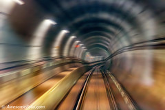 Passing Through the Tunnel of Time (james c. (vancouver bc)) Tags: train underground subway red orange yellow tunnel motion blur railroad city car rail vancouver bc britishcolumbia canada speed fast flyover railway passing movement trail dynamic urban way zoom building commute commuter drive down elevated metro metropolitan moving skytrain outdoor perspective rapid route speedway town transport transportation travel velocity
