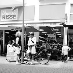 Talk (MLopht Photography | Dortmund) Tags: nrw ruhrgebiet dortmund hörde dortmundhörde streetfotografie streetphotography streetshot mensch frau einkaufszone fusgängerzone blumengeschäft blumenrisse haus laterne fahrrad marktplatz sony alpha 6300 ilce sonyalpha6300 ilce6300 sigma 19mm sigma19mm schwarzweis blackandwhite bw