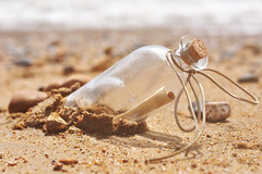 Message in a bottle washed up on the beach in the morning (Martyn.Hayes) Tags: stilllife closeup wet water wetsand saltwater sea shore ocean waves beach coast lowtide macro sand message mystery letter mail writing bottle messageinabottle ribbon cork glass pirate paper old history