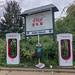 Überfüllter Mülleimer und Umweltverschmutzung zwischen zwei Tesla Supercharging E-Ladesäulen für Elektroautos
