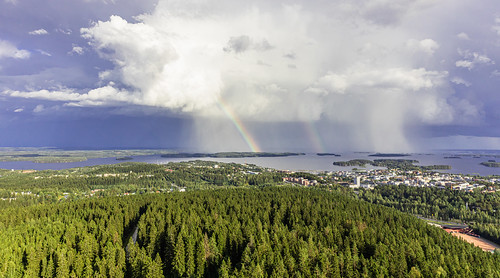 Rainbow and rain at the same time over a lake