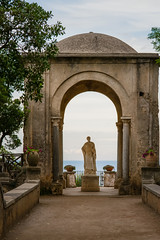 Arch with a statue at the entrance to the Terrace of Infinity or Terrazza dell'Infinito, Villa Cimbrone, Ravello  village, Amalfi coast of Italy (OLF Picture) Tags: romanstatue statue terrazzadellinfinito terraceofinfinity ravellovillage architecture door building entrance arch church stone old history ancient gate monument religion medieval europe italy monastery wall arches travel historic cathedral art culture city antique historical famous heritage civilization landmark archeology column ruin temple tourism sculpture sky woman sea blue christ marble outdoors