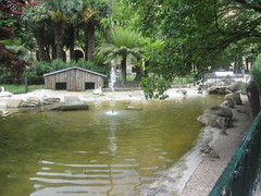 Pond in the Park, Plaza de Guipuzcoa (d.kevan) Tags: squaresandroundabouts parksandgardens sansebastian spain plazaguipuzcoa donostia guipuzcoa grass plants trees paths foliage arches railing pond rocks reflections birds swans enclosure ripples waterspout fountain swanhouse