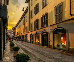Varese Evening (mswan777) Tags: street building architecture window shutter store sky sunset cloud light travel varese italy apple iphone iphoneography mobile shadow evening yellow orange glow city urban outdoor