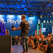 Gamescom Event: Man on stage handing out merchandise shirts to a crowd