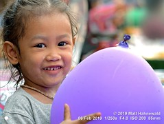 2016-12b World's Future 2019 (12) (Matt Hahnewald) Tags: matthahnewaldphotography facingtheworld people head dirty face eyes catchlights childreneyes orientaleyes epicanthicfold mouth teeth expression lookingatcamera eyecontact smile hair disheveled unkempt airballoon blue holding bothhands parentalconsent conceptual diversity humanity playing enjoyment joy upbringing childhood optimism downtown chinatown bangkok thailand asia asian thai person one female child little girl nikond610 nikkorafs85mmf18g 85mm 4x3ratio resized 1200x900pixels horizontal street portrait halflength closeup cropped seveneighthsview sidewaysglance outdoor colour posing cute authentic smiling happy scamp