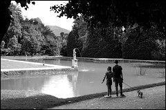 Two children and little dog watching a baroque statue. (Starej Grafik) Tags: park water trees mountains children dog hellbrunn salzburg austria statue pond baroque tranquillity calm summer fujifil fujifilmx100f x100f bw blackwhite bwphoto bwphotography