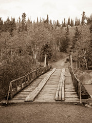 Canyon Creek Bridge In Sepia (http://fineartamerica.com/profiles/robert-bales.ht) Tags: architecture bridge canada forupload places wood river wooden water landmark scenic scenery riverbank ancient transportation structure constructions alsekriver miners gold goldrush canyoncreek alaskahighway usarmy engineers pioneerbridge yukon robertbales reflections greenlandscape blue trees forest sepia