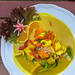 Asian Food: Colorful tumeric-curry with oranges, cauliflower, broccoli and carrots on a wooden table