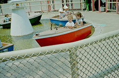 Boat Ride, Six Flags Great Adventure Amusement Park, Jackson Township, NJ (2 of 2) (gg1electrice60) Tags: sixflags greatadventure amusementpark amusements jackson jacksontownship newjersey nj unitedstates usa us america boatride boat children kids kiddierides myson carnivalrides minoltamaxxim5000camera minoltacamera filmcamera 35mmfilm colorprintfilm colornegativefilm singlelensreflexcamera slr toddler fencing oceancounty sixflagsboulevard sixflagsblvd 6flagsblvd countyroad537 countyrd537 cr537 monmouthroad monmouthrd dualsteeringwheels frontseat vehicleride water