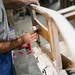 Arbeiter schleift einen Stuhl mit Schleifpapier