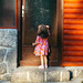 A little girl in a glamorous dress knocking on a vintage door