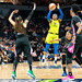 Arike Ogunbowale shoots the ball over defending Lynx players