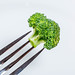 A piece of fresh broccoli on a fork on a white background