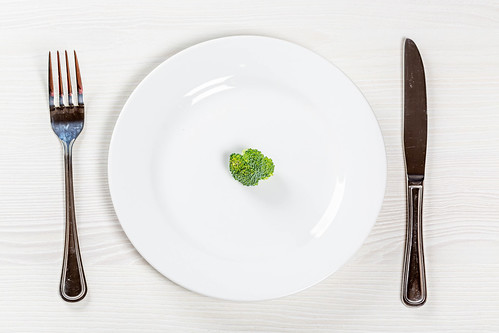 A small piece of green broccoli on a white plate as a symbol of weight loss