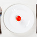 Red small tomato on a white plate with Cutlery. The concept of diet