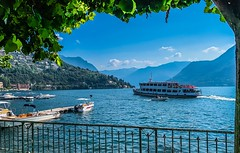 Lake Como Tour Boat (mswan777) Tags: shore coast fence tree leaf ship boat harbor mountain sky cloud green blue tourism apple iphone iphoneography mobile lake como italy travel outdoor scenic