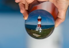Small World (Karen_Chappell) Tags: ball round circle glass nfld lighthouse red green blue white portdegrave newfoundland canada eastcoast atlanticcanada avalonpeninsula canonef24105mmf4lisusm hand refraction orb sphere stilllife conceptionbay bokeh
