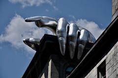 Under my thumb (remiklitsch) Tags: sculpture building silver hand montreal oldport phicentre remiklitsch city art urban nikon