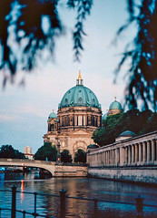 across the water (portrait) [berlin 7/45] (Andrew.King) Tags: cathedral berlin sunset evening golden hour blue summer water museum island church trees framing frame bridge spree river reflections reflection sky clouds portrait nion f3 f3hp ektar 100 film