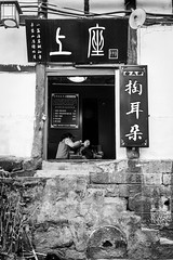 Behind the curtain (Go-tea 郭天) Tags: chongqing républiquepopulairedechine window private privacy clinic ears cleaning duty busy patient traditional tradition speciality women ladies frame framed in out inside indoor open opened business health healthy 2 together work working clean institute wall facade street urban city outside outdoor people candid bw bnw black white blackwhite blackandwhite monochrome naturallight natural light asia asian china chinese canon eos 100d 24mm prime
