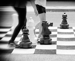 Playing Field (Demmer S) Tags: game chess outdoors chessboard chessplayers games shoppingmall suburban mall playingchess players fun challenge competition competitive play sport rook bishop pawn king queen knight boardgame checkered board street streetphotography people peoplewatching shootthestreet streetlife streetshots documentary citylife person urban outside urbanphotography urbanexploration creativeedit filtereffect bw monochrome blackwhite blackandwhite blackwhitephotos blackwhitephoto
