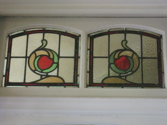 """An Art Nouveau Stained Glass Vent Window in the Bay Window of the Dining Room of """"The Gables"""" Queen Anne Villa - Finch Street, East Malvern (raaen99) Tags: thegables housename queenannehouse federationhouse queenannefederationhouse gascoigneestate stainedglass stainedglasswindow stainedglasswindows artnouveaustainedglass artnouveaustainedglasswindow baywindow finchstreet finchst queenannestyle queenanne federation window edwardian edwardiana melbourne victoria australia domesticarchitecture house home architecture melbournearchitecture housing 20thcentury twentiethcentury artnouveau nouveau 1900s 1902 malvern eastmalvern artsandcrafts artsandcraftsmovement artscraftsmovement artscrafts architecturallydesigned beverleyussher henrykemp ussherandkemp ussherkemp lawrencealfredbirchnell lawrencebirchnell detail interior room diningroom fruit leaves vine orange green red flowers floral flora"""