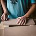 Junger Arbeiter schleift ein Stück Holz