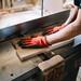 Erfahrener Tischler bearbeitet ein Stück Holz mit der Hobelmaschine