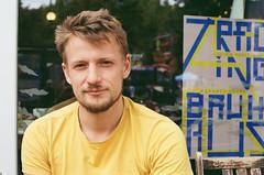 Sebastian at the Café (FrankStehl) Tags: portrait male film 35mm 50mm kodak canona1 inhabitant bewohner 14 noedit 56 5014 guy buddy blue man face yellow mann