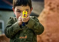 Fire away...!! Fire away...!! (Lorrainemorris) Tags: peace titanium portrait streetphotography zeiss zeissbatis85 sony boy gun candid child