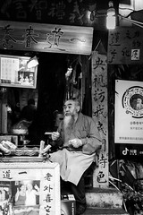 The grandmaster (Go-tea 郭天) Tags: chongqing républiquepopulairedechine old man wisdom age beard long wrinkles master ancient shop business duty work working busy seller sell selling portrait seated street urban city outside outdoor people candid bw bnw black white blackwhite blackandwhite monochrome naturallight natural light asia asian china chinese canon eos 100d 24mm prime