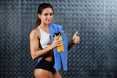 Attractive fitness woman with bottle and towel indoor portrait. (teevea) Tags: fit fitness gym sport girl portrait lifestyle healthy water drink indoor bottle young person beautiful trainer health adult female woman training smile people athletic attractive happy beauty one pretty recreation racetrack modern sporty cardio mineral slim running moonwalker runner muscles jogging cheerful equipment simulator run holding club figure smiling break