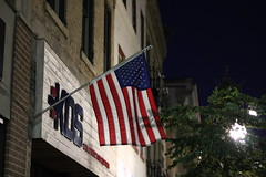 (jbouikidis) Tags: flag downtown street sky lowangleview urban buildings structure night lowlight abstract architecture contrast dark america stores