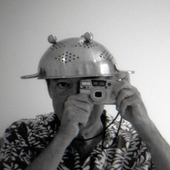 reflected self-portrait with Pentax Espio 140M camera and holey hat (cropped) (pho-Tony) Tags: square cameraselfportraits agfacopex pentaxespio140m pentax espio zoom compact autofocus point shoot pointandshoot analog analogue japan japanese 35mm film 38mm140mm 38mm 140mm 38mmto140mm agfa copex rapid agfacopexrapid microfilm copy contrast iso50 rodinal collander