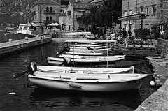 The Boats of Kotor  (Tri-X 400) (Harald Philipp) Tags: montenegro kotor seafront boats water harbor people sidewalk city street ancient historic oldtown nikon fm3a 55mm 135 35mm film analog trix iso400 d76 blackandwhite monochrome bw contrast europe tourist tourism
