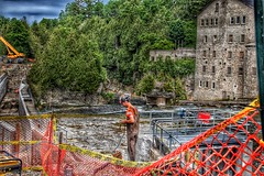 Elora Ontario - Canada  - Repairing The Falls - Old Mill (Onasill ~ Bill Badzo) Tags: elora ontario canada grand river reflection commercial buildings back wellingtoncounty travelday trip tourist bus travel coach site seeing attraction nrhp heritage dam limestone architecture victorian queenanne style clouds sky onasill canon sl1 rebel sigma macro 18250mm waterfalls repair worker man hdr oldmill construction skyclouds