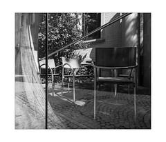 Secluded Veranda (Thomas Listl) Tags: thomaslistl blackandwhite biancoenegro noiretblanc monochrome layer glass window naturallayer chairs light shade veranda reflection grey lines diagonal cozy