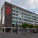 E-Ladestation am Kölner Verkehrsunternehmen:  Bürohaus der KVB mit großem, roten Logo an der Hauswand