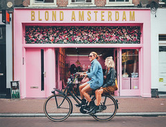 Going blonde (The Rolling Spoke) Tags: bike bicycle bici bicicleta bicicletta bisiklet cycling cycle fiets fahrrad velo ride street streetphotography candid girl girls together hitch double riding back rack side saddle sidesaddle dutch style restuarant cafe pink depijp amsterdam hip