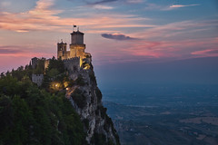San Marino and the sunset (Luís Henrique Boucault) Tags: aged ancient antique architecture background building castle city cloud defence defense environment europe fortification fortress guaita heavy historic history hour illumination italian italy landmark landscape lights long marino medieval monte mountain nature night old panorama republic rocca rock roof san scene sky summer sunset tower town traffic tree view wall
