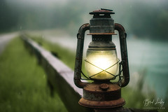 Lantern At The Lake (Brad Lackey) Tags: lantern vintage metal glass oil lake wood guardrail rain fog summer storm forest green brown bokeh nikon35mmf18g d7200
