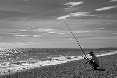 The Angler (daveseargeant) Tags: dungeness kent seaside coastal coast fishing fisherman angler monochrome blackwhite black white nikon df 50mm 18g sea water