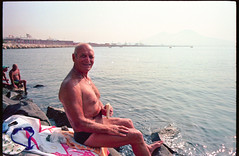 (Going Bananas) (Robbie McIntosh) Tags: leicamp leica mp rangefinder streetphotography 35mm film pellicola analog analogue negative leicam elmarit analogico leicaelmarit28mmf28iii elmarit28mmf28iii dyi selfdeveloped filmisnotdead autaut candid bellinifotoc41 kodakportra160 kodakportra portra kodak beach tan seaside bathers strangers swimsuit man summer summertime speedo portrait pose