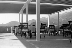Dinner Will Be Served   (Tri-X 400) (Harald Philipp) Tags: montenegro svetistefan dining chairs tables mountains nikon film fm3a trix iso400 d76 ais adriatic
