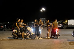 Boys, girls and bikes (Alizarin Krimson) Tags: youth young teens teenagers crossroads urban greece lesvos lesbos plomari nightshot night darkness bikes motorcycles flirting street girls boys
