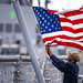 USS Billings (LCS 15) lowers the American flag as the ship gets underway from Naval Station Mayport