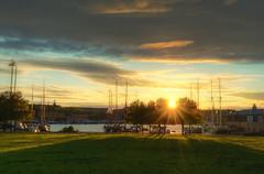 Golden Game Park (henriksundholm.com) Tags: landscape sunset city urban grass lawn shadows sun sunbeams lensflare clouds sky djurgården boats ships trees flag hdr scenery color warm stockholm sverige sweden