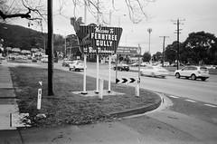 Welcome to Ferntree Gully (Matthew Paul Argall) Tags: canonsnappy20 fixedfocus 35mmfilm kentmerepan100 100isofilm blackandwhite blackandwhitefilm sign road street